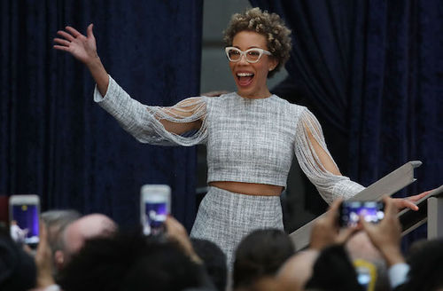 Black woman with blonde hair in white glasses and grey blouse and skirt in front of dark blue curtain and behind people with black and grey hair