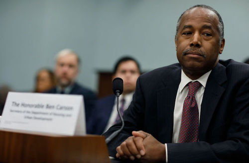 Ben Carson. Black man in black suit and red tie sits with microphone.