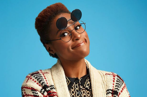 Black woman with brown hair in black glasses with black shades and red and brown sweater and black shirt with white pattern in front of blue background