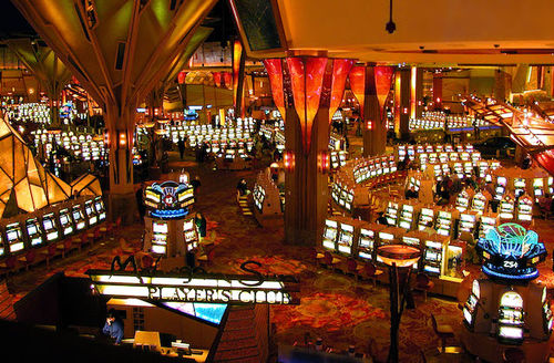 Brown and orange casino floor with yellow lights on slot machines and games