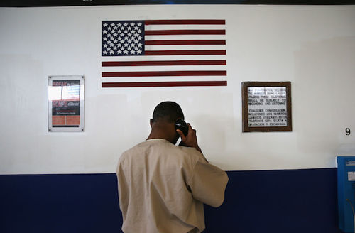A black incarcerated person makes a phone call at a reintegration center as he faces a wall painted in monochrome blue and white with the American flag at the top