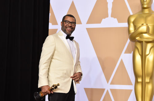 Black man with black hair and grey beard in black glasses and yellow tuxedo with black pants and bowtie holds gold statue in front of larger gold statue and white and brown wall and black curtain