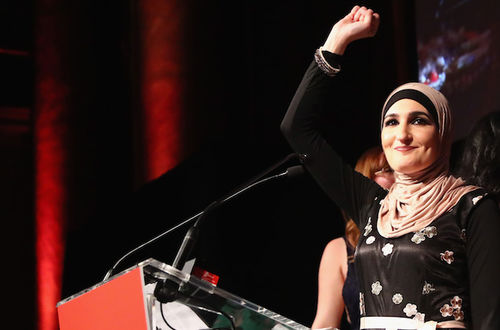 A brown woman wearing a black floral dress and a light peach hijab smiles while holding up a fist