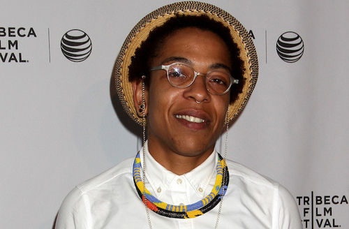 Black woman with black hair in brown hat and white shirt and multicolored necklace and glasses in front of light gray wall with black logos and text