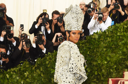 Black woman in diamond and grey bishop's hat and robe in front of photographers in black and white clothing with black cameras and green shrub and yellow wall