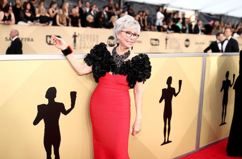 Latinx woman with grey hair and black glasses in black and red dress smiles in front of gold walls with black logos and text and audience in black and white clothing
