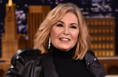 White woman with blonde hair in black shirt and jacket in front of brown and navy and white television show set