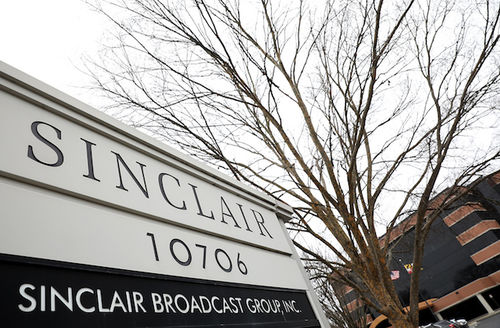 A sign for Sinclair Broadcast Group appears at the forefront of a parking lot, a tree without leaves, and the building for the corporation in the far background with an overcast sky.