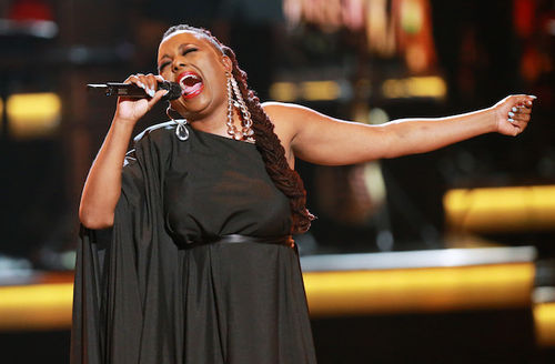 Black woman with brown hair in black dress sings into black microphone in front of blurry gold and black and brown background
