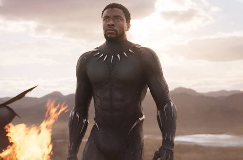 Black man in black and gold superhero suit in front of orange fire and brown mountains and blue sky with grey clouds