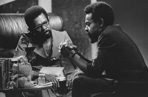 Black-and-white image of two Black men with black afros seated in front of wall