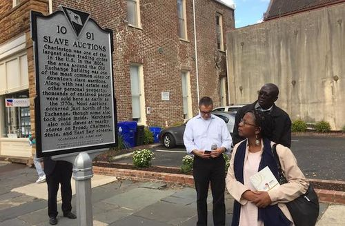 Black woman and man and White man look at grey sign in front of brown buildings