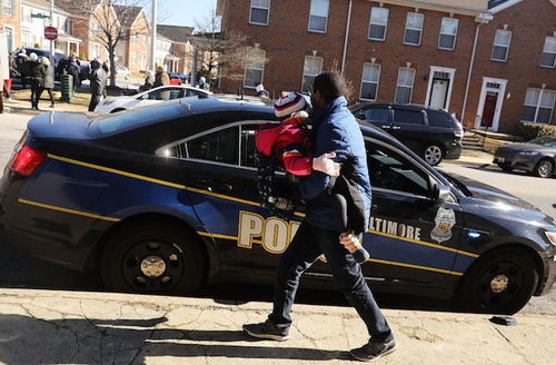 Black man holding child in pink coat walk by dark blue Baltimore Police Department cruiser with white and yellow lettering