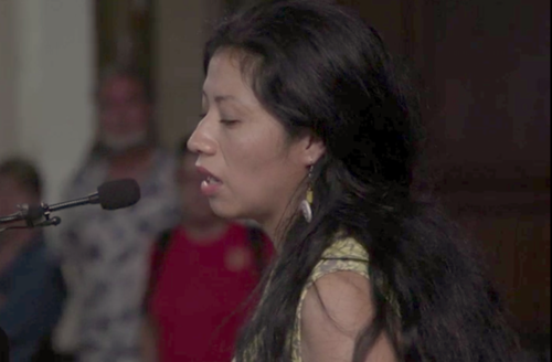 A Brown woman with long black hair and a yellow dress speaks into a microphone at a church