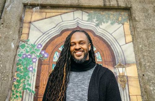 A Black man with long locs wearing a grey and black sweater smiles.