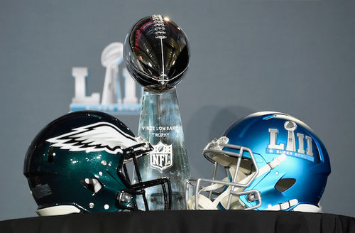 Green and blue football helmets flank silver trophy in front of dark grey wall