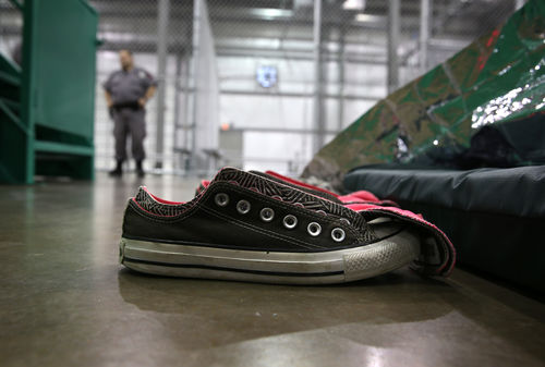 A pair of black sneakers are in focus in a detention center and a security guard stands in the background.