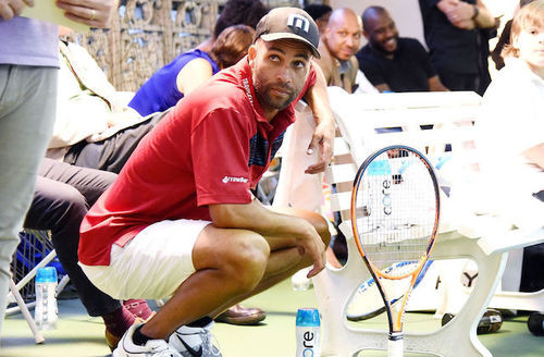 James Blake. Black man in red polo shirt, white shorts, black hat