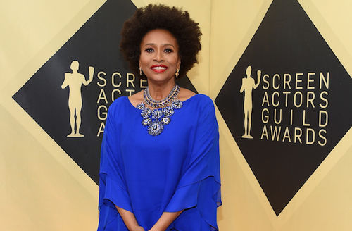 Black woman with black and brown afro in blue dress with blue jewelery in front of golden wall with black text