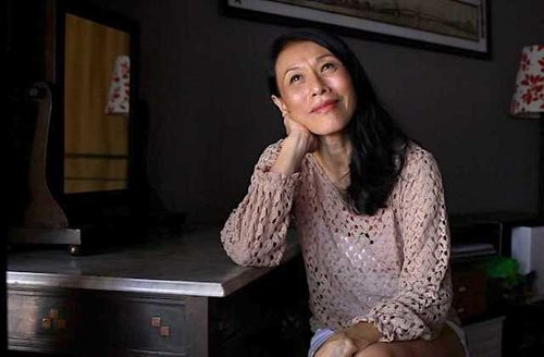 Asian woman with black hair in pink sweater at grey desk in black room