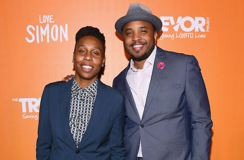 Black woman with black dreadlocks in navy suit with black and white shirt stands next to Black man in navy suit with pink shirt and grey hat in front of orange wall with white text