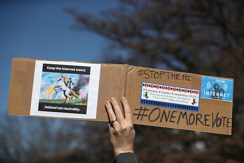 Hand holds brown cardboard sign with black text and multicolored graphics and paper in front of blue sky