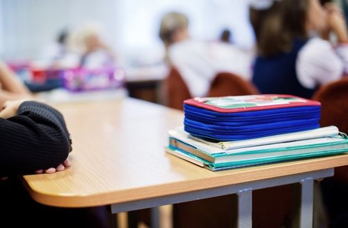 Blue pencil case sits atop teal book with white cover, all sitting on a child's desk in a classroom; only the desk is in focus