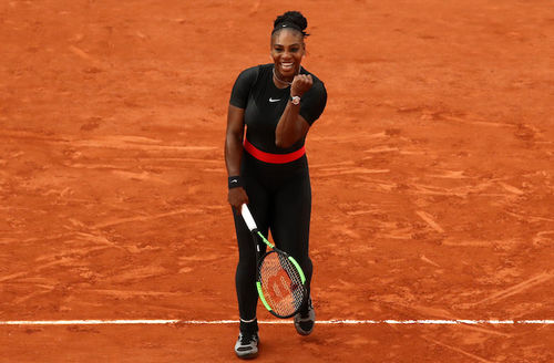 Black woman with black hair in black athletic suit with red stripe holds black and green and white tennis racket and smiles while standing on brown tennis court with white line