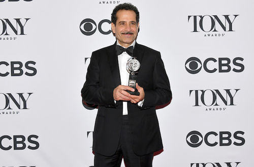 Brown man with black hair and moustache holds silver award statue while wearing black and white tuxedo in front of white wall with black text
