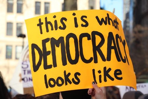 """A handwritten sign that says """"This is what democracy looks like"""""""