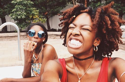 Two young Black women, one with a red tank top and light brown-dyed natural hair, the other in a multicolored strapless shirt and reflective sunglasses