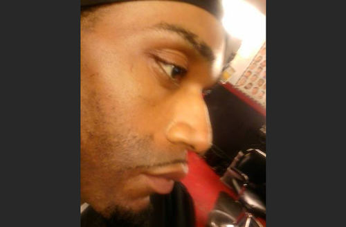 Black man in profile wearing a black durag on head, red and black furniture behind him.