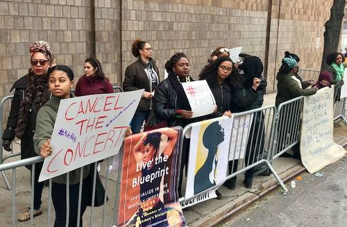Black women and girls in black and green jackets hold white and orange signs with multicolored text behind grey barrier in front of grey building