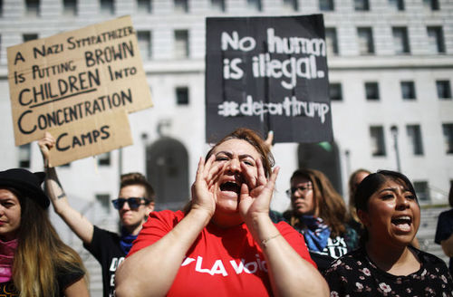 """Protesters outside. Brown woman in front wears red shirt, white and black sign behind her reads """"No human is illegal. #DeportTrump."""""""
