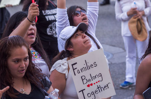 """Brown people protest outside. One sign reads, """"Familes belong together."""""""