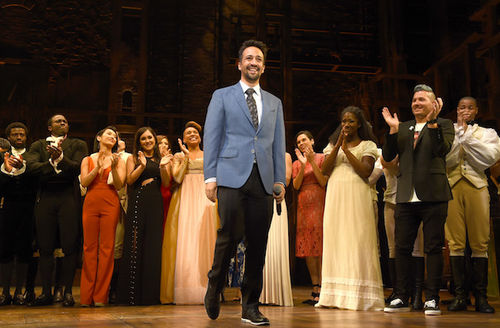 """Cast of """"Hamilton"""" in multicolored costumes stands and applauds behind Lin-Manuel Miranda in blue blazer and grey tie and black pants on brown stage"""