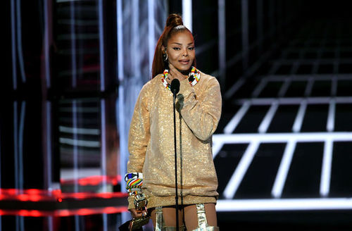 Janet Jackson. Black woman wearing shimmery gold sweater, rainbow-colored beaded necklace and bracelets stands on a stage