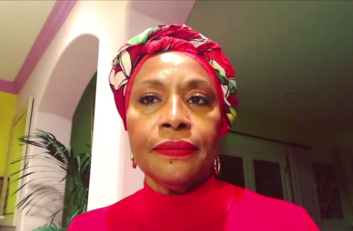 Jenifer Lewis. Brown woman wearing red shirt and red, white and green scarf on head and hoop earrings