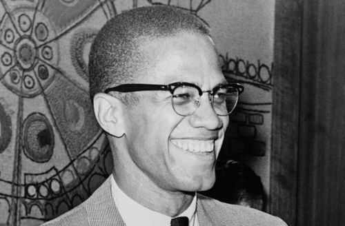 Black-and-white photograph of Malcolm X in glasses and suit with white shirt in front of patterened wall