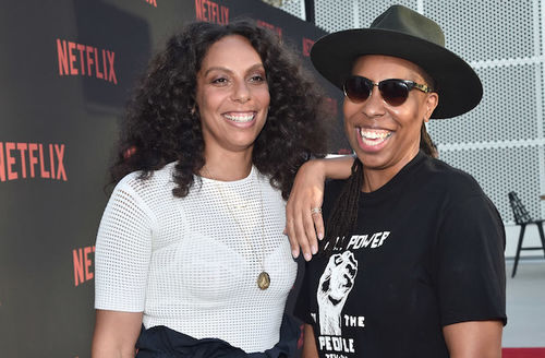 Melina Matsoukas in white shirt and dark navy pants smiles next to Lena Waithe in black sunglasses and t-shirt with white text and raised fist and green hat