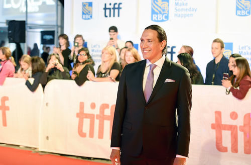 Indigenous man with black hair in grey suit with purple tie smiles in front of crowd behind red carpet and white wall with orange text