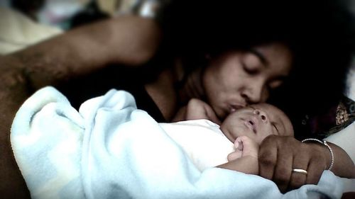 A Black woman with a large afro kisses a newborn wrapped in a white blanket