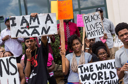 "Black people protest outside. Signs include ""I am a man,"" ""Blcack lives matter"" and ""The world is watching."""