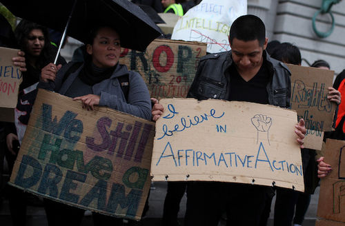 """Brown people protest outside. One board cardboard sign reads, """"I believe in affirmative action."""""""