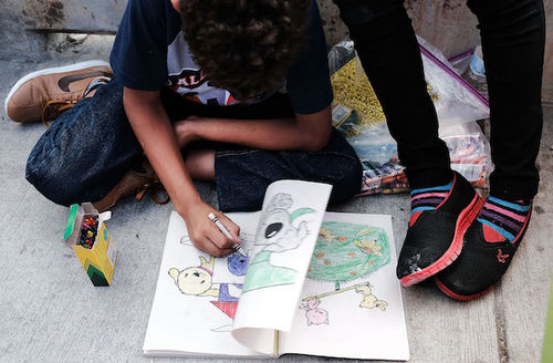 Brown child sits on ground coloring while wearing dark jeans, tan shoes and shirt in various shades of blue.