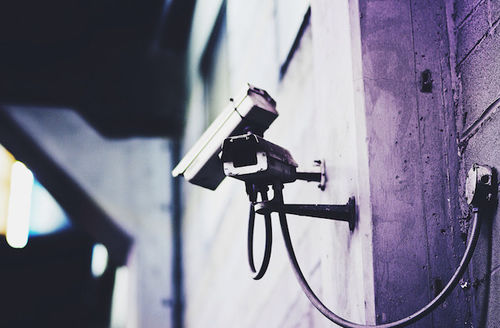 Surveillance camera mounted to a wall, all in gray and purple tones