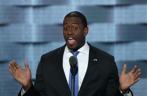 A Black man at microphone stand with his mouth open as if to give a speech with his hands outstretched