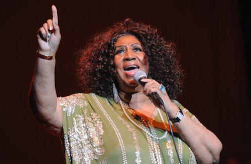 Aretha Franklin in green dress with silver embroidery holding black microphone in front of black screen