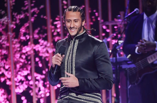 Colin Kaepernick with black cornrows in black and gold outfit holding black microphone in front of pink background