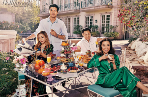 Henry Golding in blue shirt behind Constance Wu in green floral print robe next to Michelle Yeoh in green pyjamas in front of Jon M. Chu in white shirt surrounding table with multicolored food in front of white mansion and green trees
